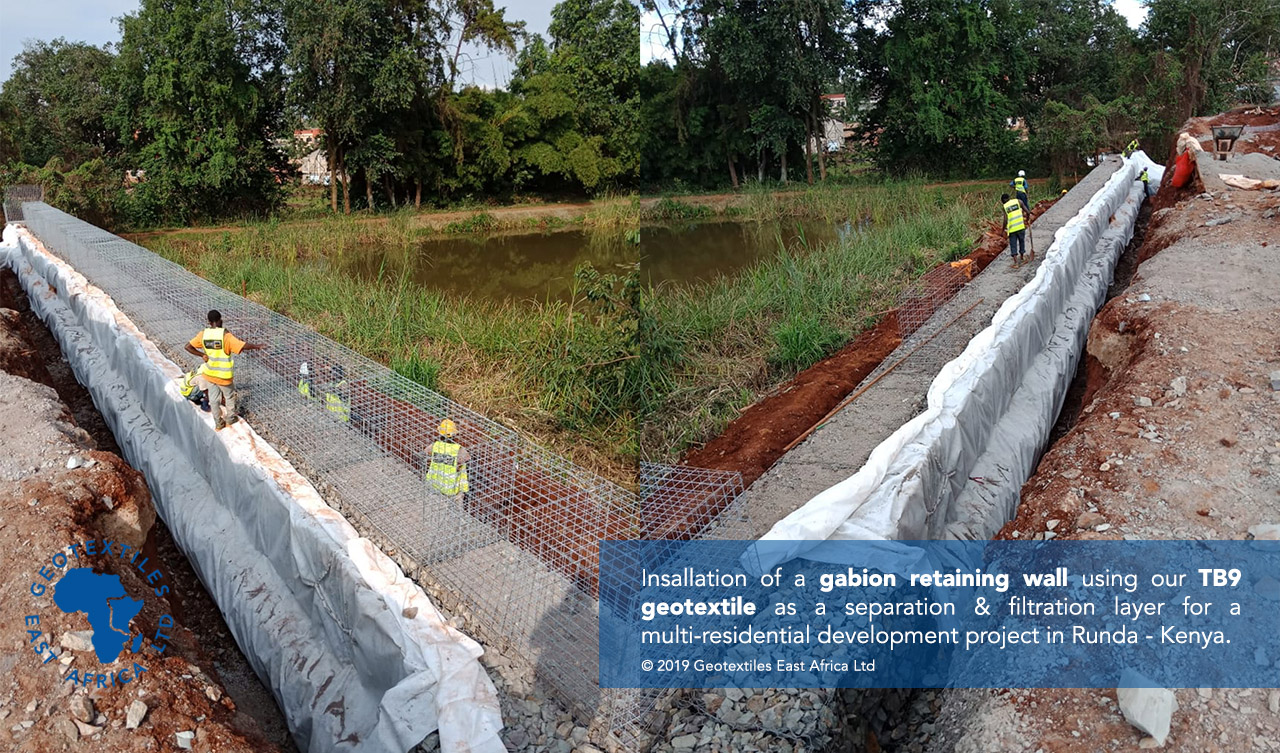 geotextile backing being installed behind gabion retaining wall